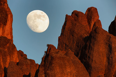A nearly full moon rises over high peaks minutes before sunset at Pinnacles National Monument, Monterey County, California , USA.