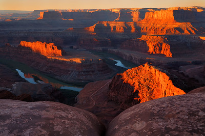 Sunrise skims the buttes and reflects into the Colorado River, Dead Horse Point State Park, Utah, USA.