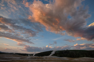 Sunset light warms clouds over geysers near Old Faithful, Yellowstone National Park, Wyoming, USA.