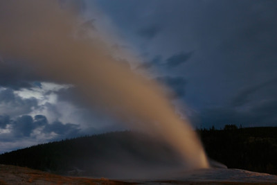 Old Faithful erupts against a stormy night sky, Yellowstone National Park, Wyoming, USA.