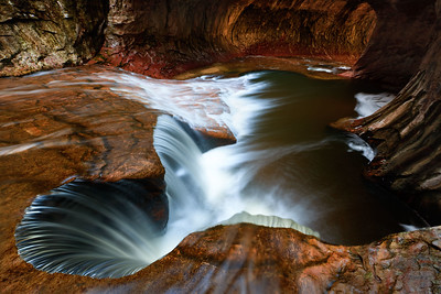 Spring runoff feeds the water levels of North Creek resulting in higher than normal flow through the Subway, Zion National Park, Utah, USA.
