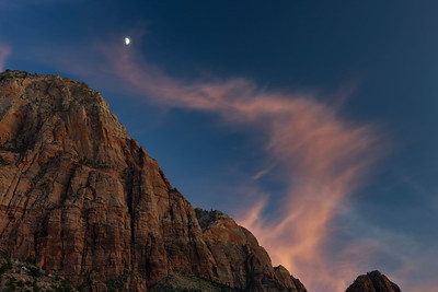 A half moon rises over The Watchman with lit cloud, Zion National Park, Utah, USA.
