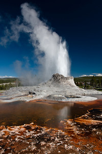 Castle Geyser is one of the larger predictable geysers in the Upper Geyser Basin at Yellowstone NP.  Castle gets its name from the cone of geyersite that forms the bulk of the geyser. The orange coloration is from bacteria that thrives in the hot water, known as Thermophiles.