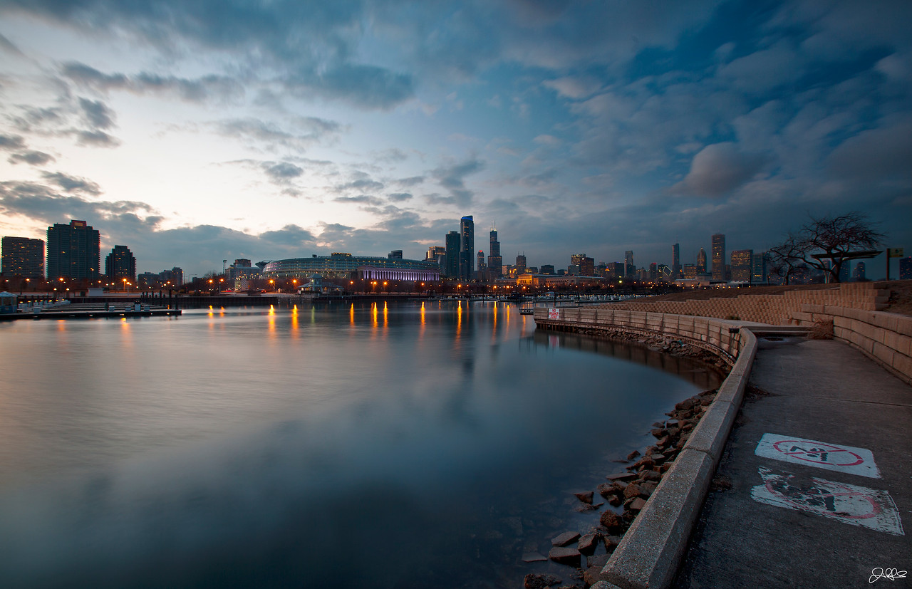 NORTHERLY ISLAND SKYLINE<br /> <br /> A view of the Magnificent Chicago skyline from Northerly Island. Northerly Island used to be a small airport called Meigs Field that operated from 1948 until March 31, 2003, when it was destroyed in a covert operation at night by Mayor Richard Daley. The land is now part of the Chicago Park District and has a beach area, concert venue, and wildlife preserve. Soldier field, where the Chicago Bears play is visible in this photo with the purple lighting around the columns left center...