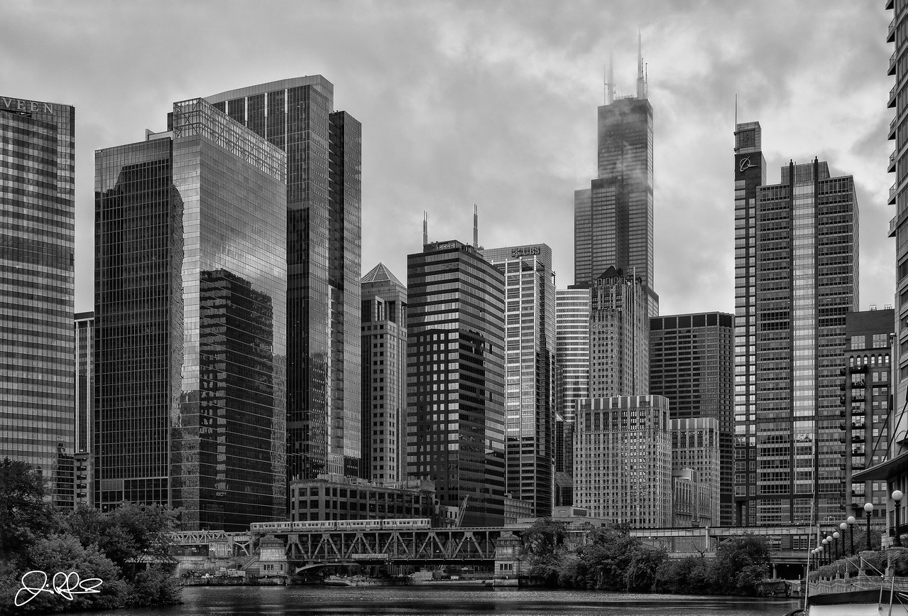 North Branch in B&W...<br /> <br /> This view of the north branch of the Chicago River is hands down one of my favorites. Its a great view of the financial district of Chicago which includes building such as the Willis Tower (It will always be the Sears Tower to me...), UBS Tower, Beoing Headquarters, and the Civic Opera House. On this morning, the distant sounds of L-Trains crossing the bridge in the distance broke the silence every few minutes while storm clouds shrouded the massive Willis Tower from view. I waited patiently hoping the clouds would break enough to see the tower and finally after about 30 minutes or so, the clouds broke. I only had about 5 seconds or so to capture this image before the storm clouds once again blocked her from view.