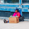 People in Ecuador - street beggar/vendor selling candy and other small items.