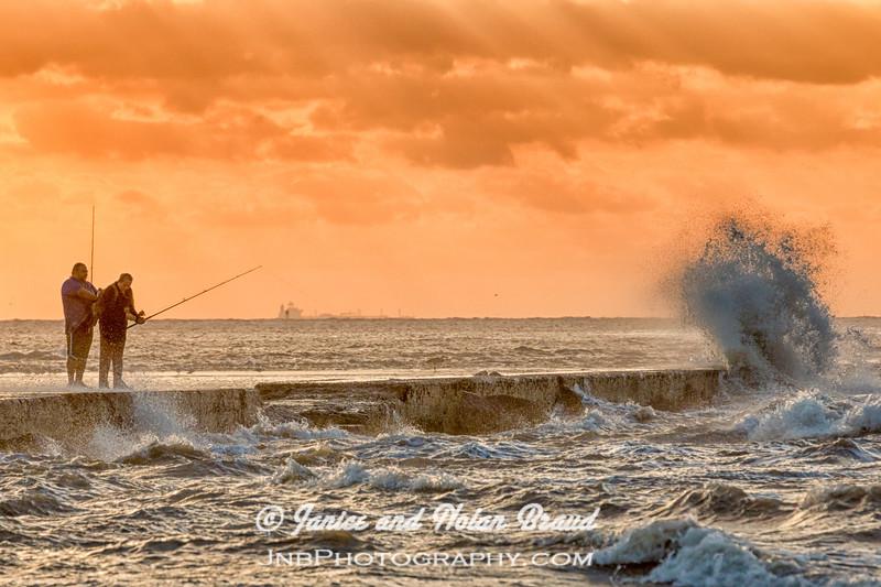 Fishing amid dramatic wind and waves at sunrise on Galveston East Beach.