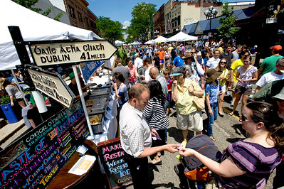 "The manager of Conor O'Neill's pub sells tickets to a customer enjoying ""A Taste of Ann Arbor,"" a festival to showcase Main Street restaurants in Ann Arbor, MI.  The Black Pearl restaurant and their fish tacos won best of show."