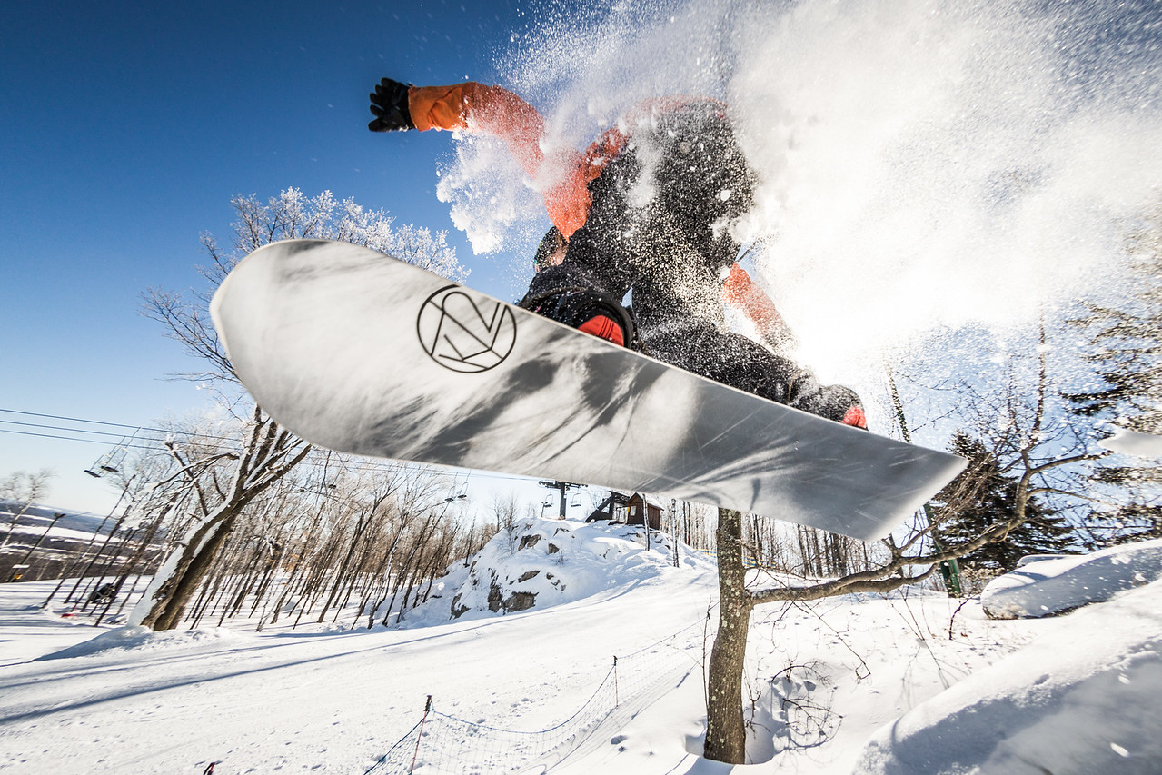Closeup of a snowboarder going off of a jump