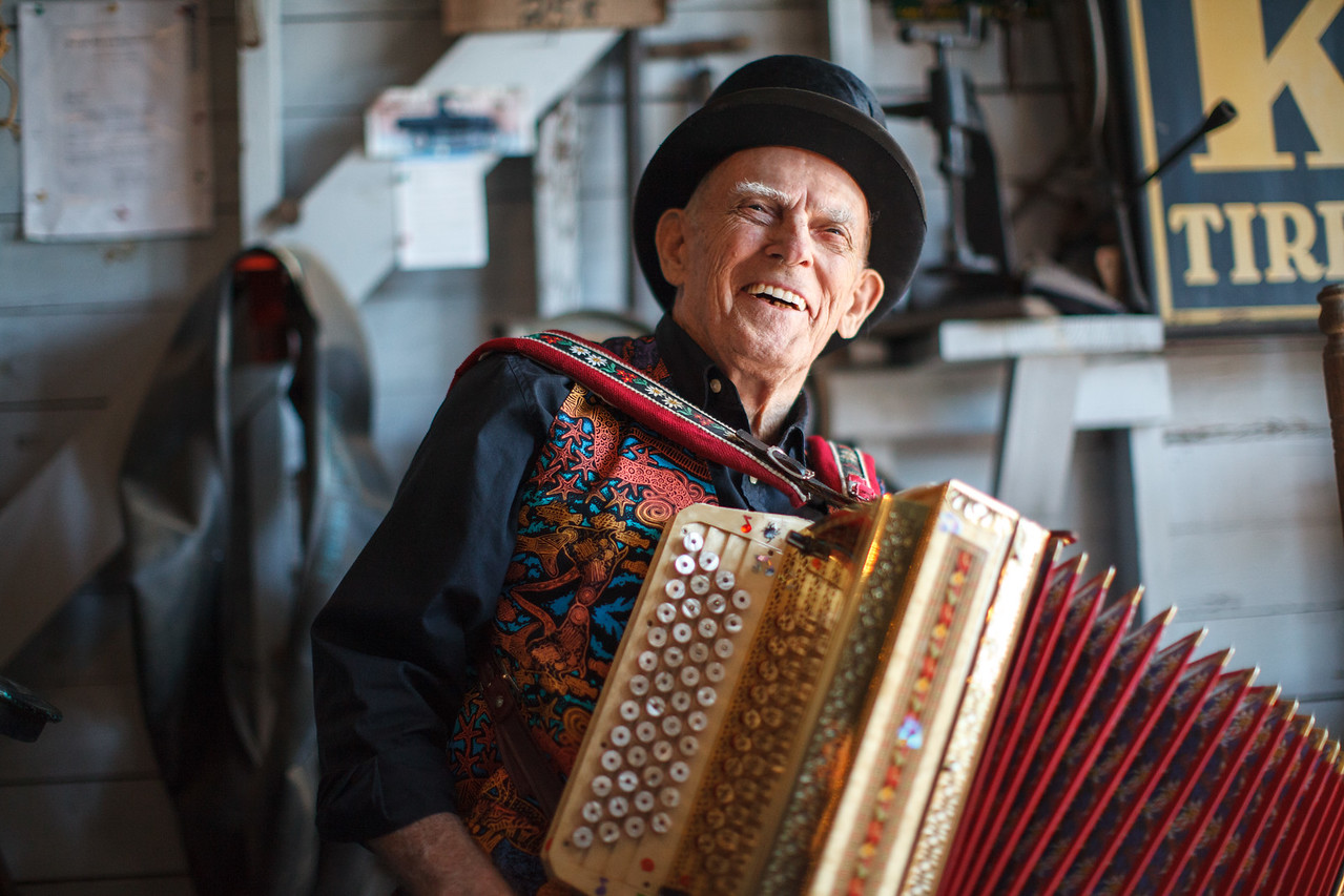 A man smiling while holding an accordion.