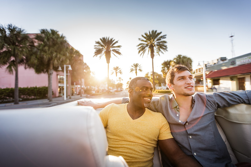 Gay couple in the back of a convertible.