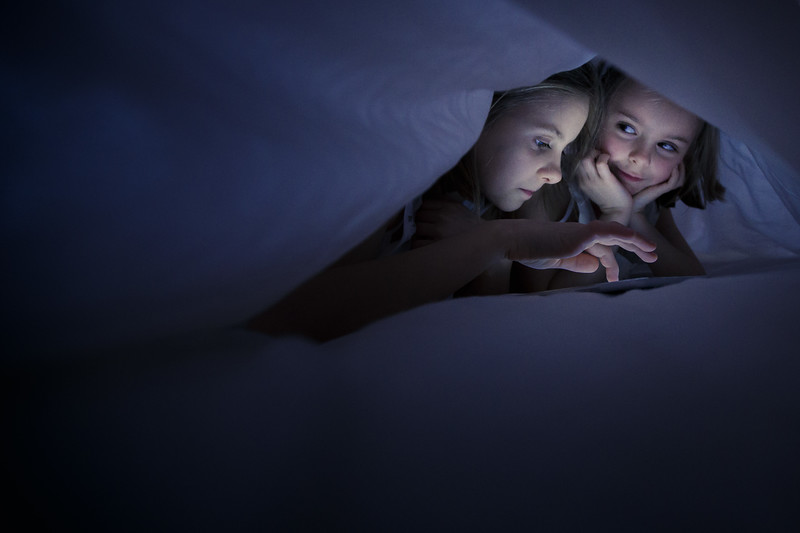 Sisters playing on ipad under the sheets at night.