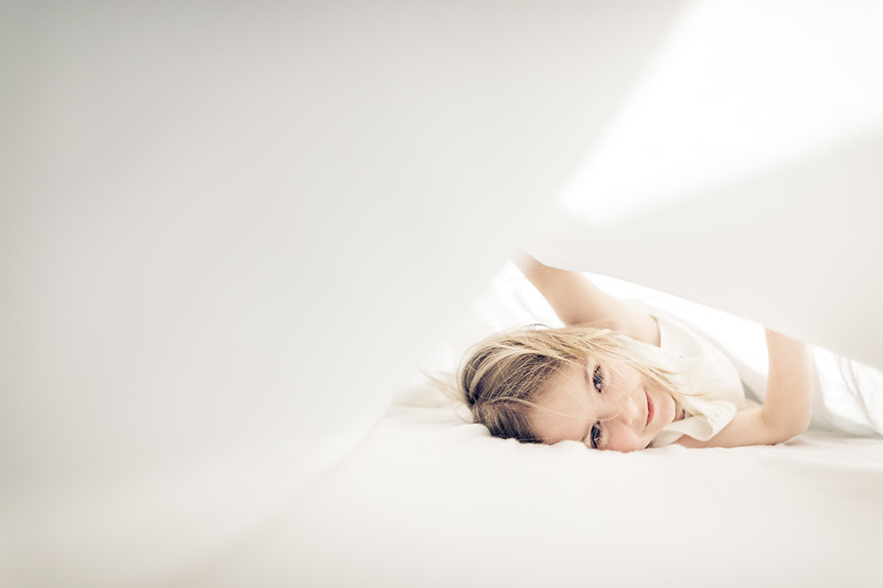 Little girl playing under white sheets