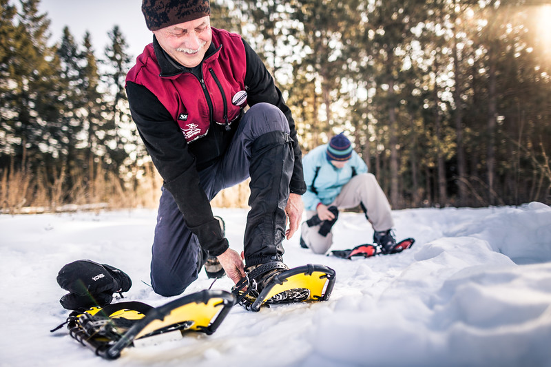 Two men putting on snow shoes.