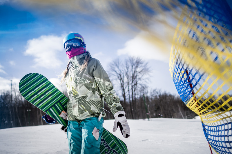 A girl getting ready to snowboard.