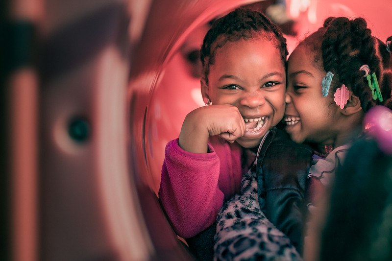 Two girls smiling in play slide