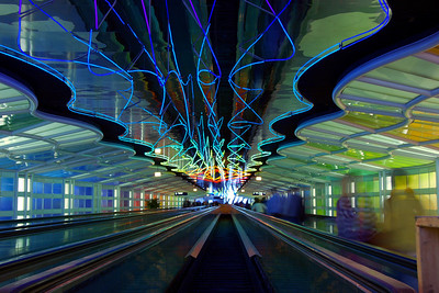 Abstract image of people on the move - moving sidewalks and neon lights