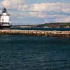 """Spring Point Ledge Lighthouse on a breakwater ledge in Casco Bay, at Portland Harbor, Portland, Maine, was established in 1897. It is one of only a few of the """"sparkplug"""" type lights in Maine. Though they are considered to look like the ignition spark plugs used gasoline or diesel engines, they are designed to handge extreme weather, including gale-force winds, tremendouse waves, ice and whatever stresses nature can invent. The original light has stood against these forces for more than a century, while guiding mariners past the long breakwater shielding Portland Harbor."""