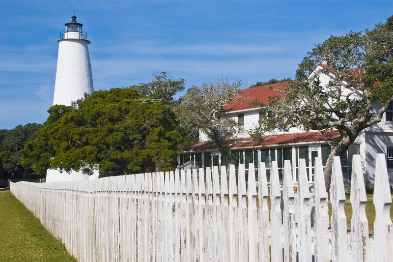 """Located in the fishing village of Ocracoke on the island of Ocracoke, this is the oldest operating lighthouse in North Carolina and is equipped with a fourth-order Fresnel lens.<br /> The present structure is the third. In 1798, a 54-foot wooden tower was built on the Ocracoke Inlet entrance where Edward Teach, otherwise known as """"Blackbeard the Pirate,"""" lived at one time. The channel shifted, rendering the lighthouse ineffective. It was replaced by a light vessel in the inlet in 1820, but by 1822 this structure was also rendered useless by shifting sands, and Congress authorized the money to build the present tower which stands 75 feet tall. The lighthouse was cemented and whitewashed in 1868, giving it the appearance it has today. <br /> <br /> Originally fueled by whale oil, it is now lit by automatic electric power and shines 14 miles out to sea."""