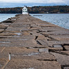"""Rockland Breakwater Lighthouse, was built in 1888 on a mile long """"breakwater"""" in Rockland Harbor at Rockland, Maine. The small, square, 25 foot tower stands at the end of a long platform of squared off granite blocks created to quell the high waves rolling in from the sea in this previously unprotected harbor."""