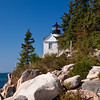 Bass Harbor Head Lighthouse on Mount Desert Island, Maine. Built in 1858, this lighthouse which clings to the side of a red rock cliff on Mount Desert Island is considered to be one of the most picturesque lighthouses in America. Best views of it are from a boat, but there is a path down the side of the cliff that rewards the adventurous with great views of the light and the channel. The original fourth-order Fresnel lens is still in place.
