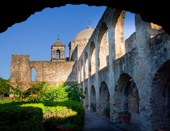 I took this photo as part of a digital photography class trip to the Missions in San Antonio.  Mission San Jose is a well preserved mission,  and on this morning we had clear blue skies, and had some fall blooms.   This shot was taken from under an arch, which framed the architecture of the mission.  This was one of the shots I took on my way to mass in the morning before my classmates arrived, giving me some good shadow lines from the arches.