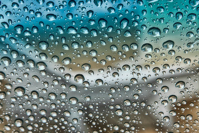 Raindrops reflecting my house...upside down...on my car windshield.