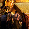 MANDALAY. MEN APPLY GOLD LEAFS TO THE BUDDHA STATUE. MAHAMUNI PAYA (PAGODA). MYANMAR. BURMA. MAHAMUNI BUDDHA.
