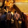 MANDALAY. MEN APPLY GOLD LEAFS TO THE BUDDHA STATUE. MAHAMUNI PAYA (PAGODA). MYANMAR. BURMA. MAHAMUNI BUDDHA.