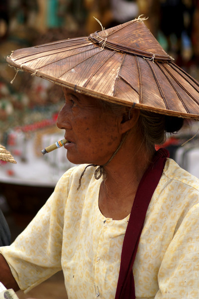 INLE LAKE. WOMAN SMOKING HER CIGAR. MARKET. BURMA.  MYANMAR.