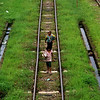 YANGON. BURMESE KIDS WALKING ON A TRAIN TRACK.