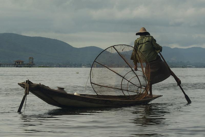 INLE LAKE. FISHER MAN ROWING HIS BOAT. SHAN DISCTRICT. BURMA. MYANMAR.