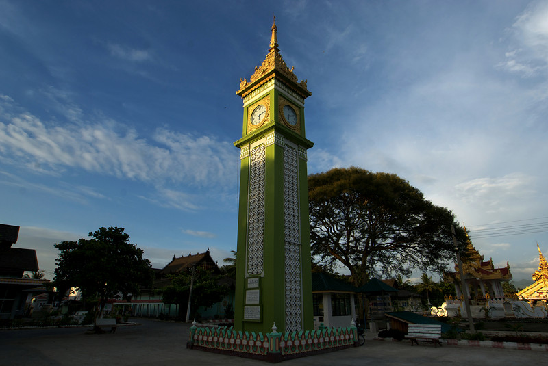 MONK UNIVERSITY. A TINY GREEN COPY OF THE BIG BEN AT THE ENTRANCE. MANDALAY. MYANMAR. BURMA.