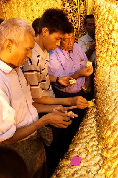 MEN APPLY GOLD LEAFS TO THE BUDDHA STATUE. MAHAMUNI PAYA (PAGODA). MANDALAY. MYANMAR. BURMA. MAHAMUNI BUDDHA.