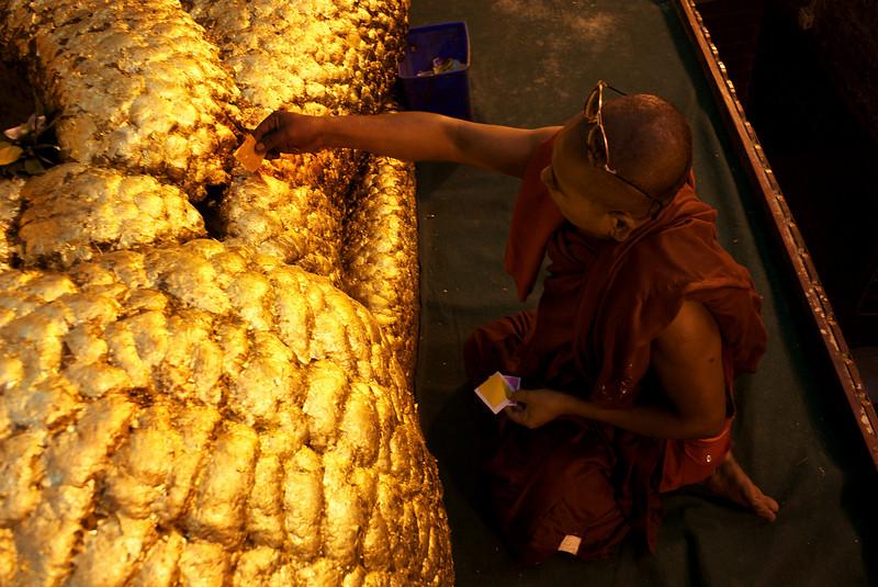 A MONK WITH SUNGLASSES APPLIES GOLD LEAFS TO THE BUDDHA STATUE. MAHAMUNI PAYA (PAGODA). MANDALAY. MYANMAR. BURMA. MAHAMUNI BUDDHA.