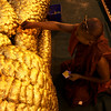 A MONK WITH SUNGLASSES APPLIES GOLD LEAFS TO THE BUDDHA STATUE. MAHAMUNI PAYA (PAGODA). MANDALAY. MYANMAR. BURMA. MAHAMUNI BUDDHA.