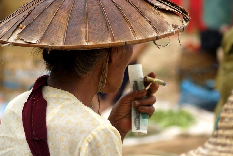 INLE LAKE. WOMAN SMOKING HER CIGAR. MARKET. BURMA.  MYANMAR.