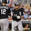 Chicago White Sox right fielder Carlos Quentin (20) is greeted at home by teammate A.J. Pierzynski (12) after hitting a home run in the third inning. The home run narrowed the gap, bringing the score Twins 3, White Sox 2 after the top of the third inning.