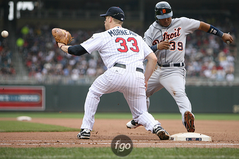 Detroit Tigers shortstop Ramon Santiago (39) is checked back to first with a throw to Minnesota Twins Justin Morneau (33) in the early innings. The Tigers went on to win the game 9-7.