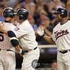 Minnesota Twins teammates second baseman Michael Cuddyer (5)and left fielder Delmon Young (21) congratulate designated hitter Jim Thome (25) after his second home runs for the night at the Seattle Mariners versus Minnesota Twins baseball game at Target Field in Minneapolis, MN. This one was his 593rd of his career went over left field fence in the seventh inning. The Mariners went on to win 8-7 in 10 innings.