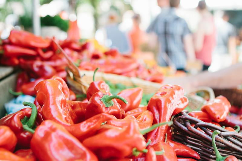 Red peppers for sale at a farmers market with out-of-focus people in the background