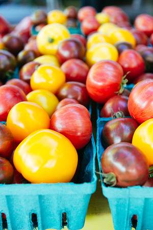 Fresh heirloom yellow and purple tomatoes in individual containers at a farmers market