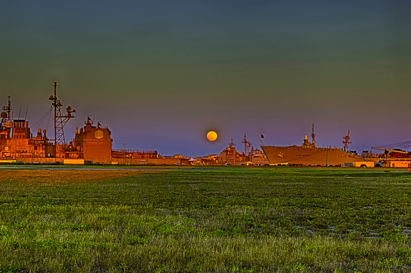 Full Moon Over Naval Station Mayport Florida.Start of Memorial Day Weekend. Moonrise/Sunset(behind). A view of the workers of freedom, those on duty only. Most ships are empty except duty sections while the shore side are on a four day weekend. Those on liberty on the way out the gate did not look back to see this. And we gave no mind to it while we served just duty and liberty Ha, Ha. We may have seen this in many forms at sea/ in a clearing of the brush/over the dunes while in the sandbox but not camera in hand to record just recorded in our minds while holding that wrench/scalpel/pen and paper writing a letter/while cleaning our rifles or sharpening our knives while we watched the day was done and our night just beginning. The ships are very a glow in orange due to a very bright cloudless orange/red sunset behind me. Scouted this location with TPE and Google Earth days before and watched the weather all day.This is not a true full moon, it is the day before. To get this kind of shot there are only two days just before the full moon a month and only 12 times a year (Unless you photoshop, which this is not.). The night of a full moon rise the sun will set an hour before. During the spring and fall the sun will rise almost exactly east and west with a full moon doing the same but summer the sun will rise to the north but the moon to the south and winter the sun to the south and moon to the north. If you had a pier/road for example perfect east and west twice a year the moon and sun will rise (set) head on and June (super moon)  sun to north moon to the south and December sun to the south and moon to north and of course sun in the morning and moon at night. A goal for the golden hour photographer would be to capture that favorite pier/road/lake those three times a year sunrise/sunset- moonrise/moonset and place them side by side. Nik Software (HDR, Define) The Photographer's Ephemeris (TPE) APP (Sunrise/Sunset-Moonrise/Moonset times and azimuths) . Canon T2i 18mm.