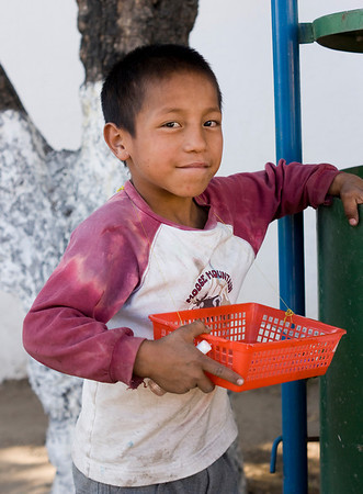Manuel is seven years old and sells chocolate on the streets of Huehuetenango. He likes to draw and holds in his hand a make-up article. He found it in the rubbish bin and used it to writer the letters on the bin.