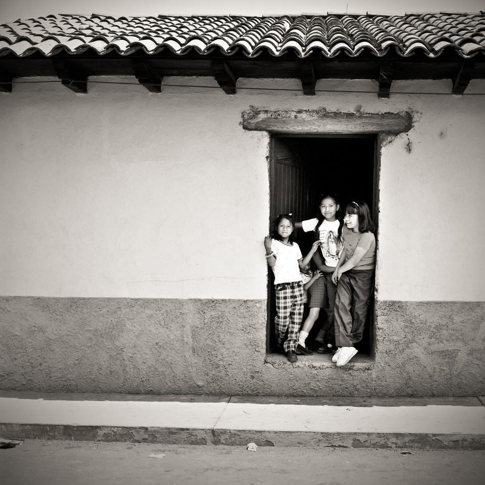 Young girls hanging out by a doorway.