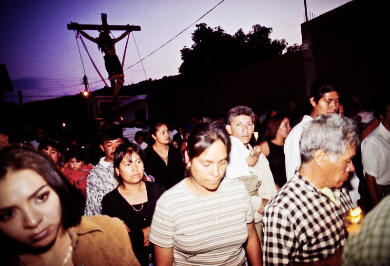 A procession of people with a cross in the blue sky.