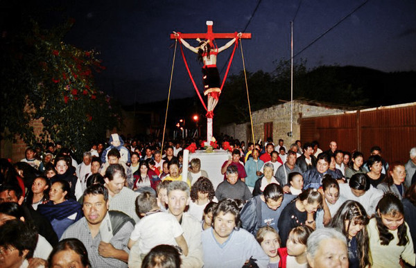 A statue of Jesus nailed on a cross is being carried by a large crowd in a procession.