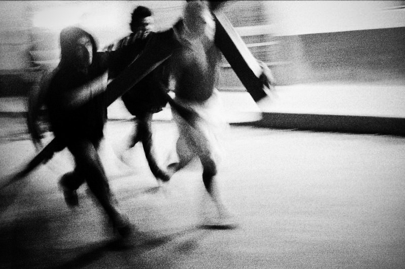 Three men running in the street at night. They are blurred by the motion.
