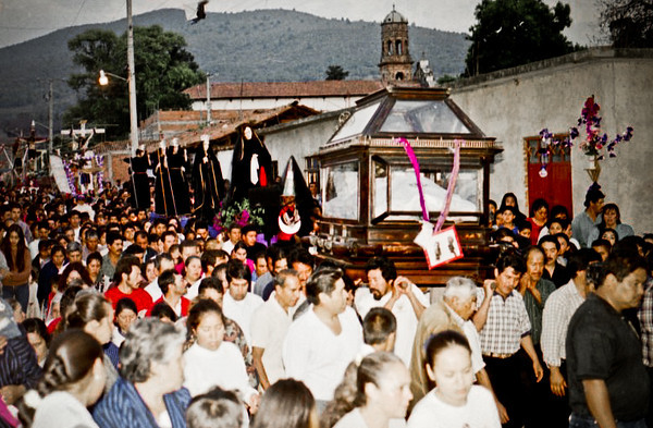 A procession of hundreds of people carring a coffin and other statues of religious figures through the streets of a small town.