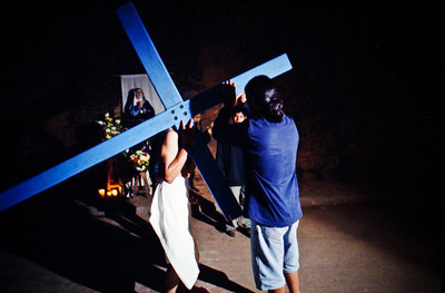 "A man helps to lift the blue wooded cross to the ""flagellente's"" shoulder."
